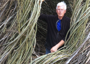 Photo of Patrick Dougherty standing inside of this sculpture A Bird in the Hand
